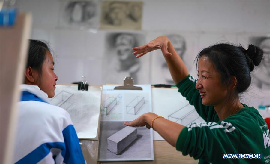 Teacher Zeng Wenping (R) instructs a student in painting at Qiyin school in Nanchang, capital of east China\'s Jiangxi Province, Nov. 26, 2018. Zeng, 43, has been engaged in special education for 21 years ever since she graduated from university. Hearing impaired students enjoy the all-encompassing heartfelt and intensive care by Zeng and consider her as more than a teacher but a sister. (Xinhua/Hu Chenhuan)
