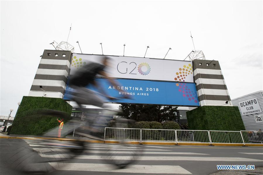 A man rides a bicycle past a banner of G20 summit outside the Costa Salguero Center in Buenos Aires, Argentina, on Nov. 27, 2018. The 13th G20 summit, under the theme of Building Consensus for Fair and Sustainable Development, will be held for the first time in a South American country from Friday to Saturday. (Xinhua/Li Ming)