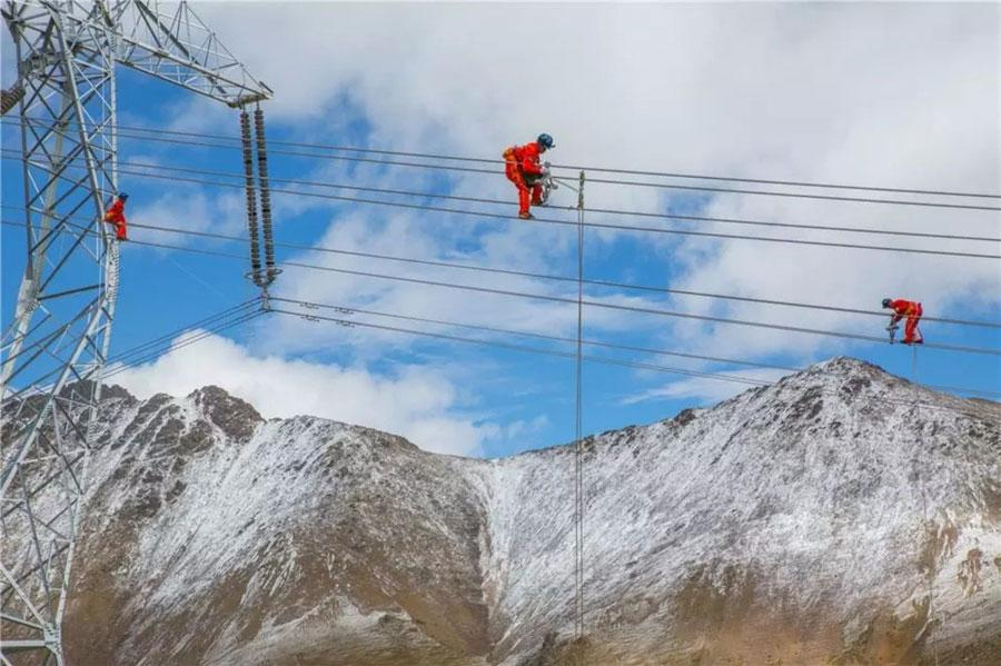 Technicians install spacers on the world\'s highest ultra-high voltage transmission project in southwest China\'s Tibet autonomous region, September, 2018. Workers involved in the project have had to overcome various challenges, including the lack of oxygen at altitudes as high as 5,300 meters above sea-level. (Photo provided by State Grid Qinghai Electric Power Company)