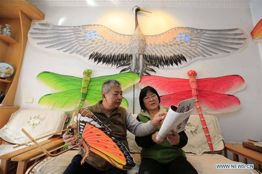 Fu Xianming and his wife discuss kites making techniques in Shijiazhuang, capital of north China\'s Hebei Province, Nov. 21, 2018. Fu Xianming, a 66-year-old craftsman, has devoted himself in kites making for 20 years. Fu and his wife have made more than 1,500 kites of various shapes since 1998. (Xinhua/Zhang Haiqiang)