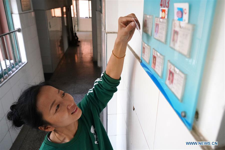Teacher Zeng Wenping rearranges students\' information at Qiyin school in Nanchang, capital of east China\'s Jiangxi Province, Nov. 26, 2018. Zeng, 43, has been engaged in special education for 21 years ever since she graduated from university. Hearing impaired students enjoy the all-encompassing heartfelt and intensive care by Zeng and consider her as more than a teacher but a sister. (Xinhua/Hu Chenhuan)