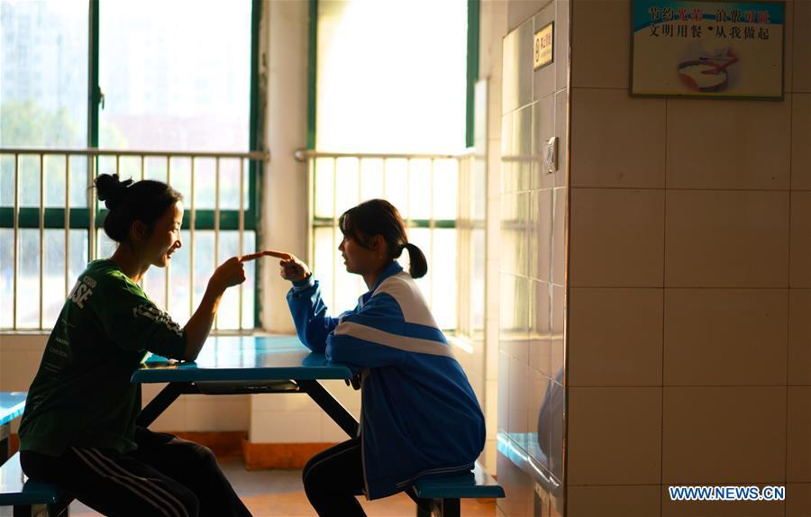 Teacher Zeng Wenping (L) comforts a student at Qiyin school in Nanchang, capital of east China\'s Jiangxi Province, Nov. 26, 2018. Zeng, 43, has been engaged in special education for 21 years ever since she graduated from university. Hearing impaired students enjoy the all-encompassing heartfelt and intensive care by Zeng and consider her as more than a teacher but a sister. (Xinhua/Hu Chenhuan)