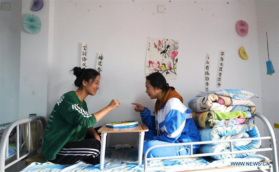 Teacher Zeng Wenping (L) plays Chinese checkers with a student at Qiyin school in Nanchang, capital of east China\'s Jiangxi Province, Nov. 26, 2018. Zeng, 43, has been engaged in special education for 21 years ever since she graduated from university. Hearing impaired students enjoy the all-encompassing heartfelt and intensive care by Zeng and consider her as more than a teacher but a sister. (Xinhua/Hu Chenhuan)