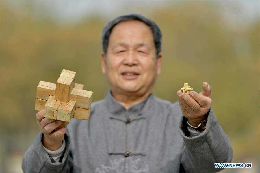 Hou Quanchen shows his self-made Kong Ming Locks in Shahe City, north China\'s Hebei Province on Nov. 28, 2018. Hou Quanchen, who is in his seventies, has devoted himself in the studying and making of Kong Ming Locks and has tried to promote this art among local residents ever since his retirement. (Xinhua/Tian Xiaoli)