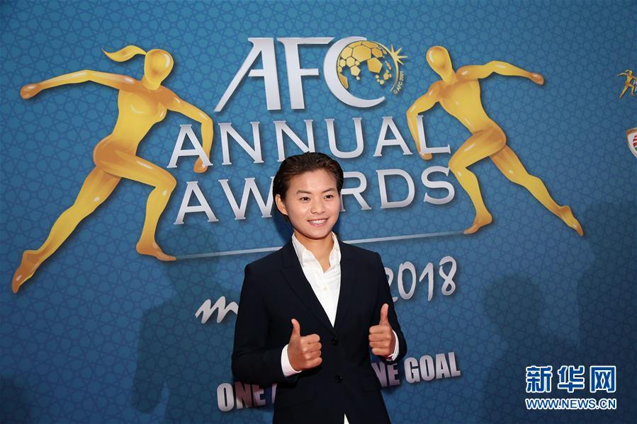 Wang Shuang poses in front of the poster of the AFC Annual Awards 2018. (Photo/Xinhua)