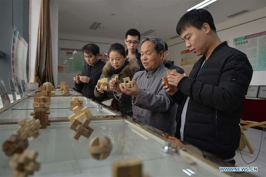 Hou Quanchen introduces Kong Ming Locks to the visitors in Shahe City, north China\'s Hebei Province on Nov. 28, 2018. Hou Quanchen, who is in his seventies, has devoted himself in the studying and making of Kong Ming Locks and has tried to promote this art among local residents ever since his retirement. (Xinhua/Tian Xiaoli)