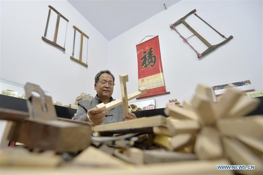 Hou Quanchen designs a Kong Ming Lock in Shahe City, north China\'s Hebei Province on Nov. 28, 2018. Hou Quanchen, who is in his seventies, has devoted himself in the studying and making of Kong Ming Locks and has tried to promote this art among local residents ever since his retirement. (Xinhua/Tian Xiaoli)