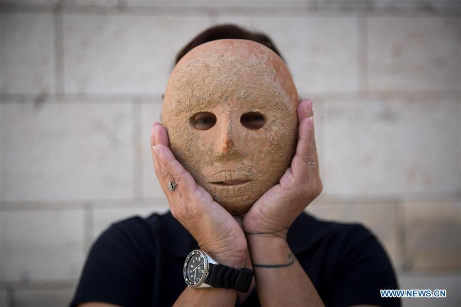 Ronit Lupu, an archeologist from the Israel Antiquities Authority (IAA), holds a stone mask at the Rockefeller Museum in Jerusalem, on Nov. 28, 2018. A rare pre-historic stone mask, dating back to the Pre-Pottery Neolithic B (PPNB) period 9,000 years ago, was discovered in the southern West Bank, the Israel Antiquities Authority said Wednesday. (Xinhua/JINI)