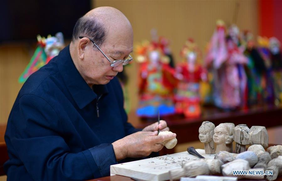 Xu Zhuchu, a national-level intangible cultural heritage inheritor of Zhangzhou wood puppet head carving, carves on a piece of wood to make puppet head at a studio in Zhangzhou City, southeast China\'s Fujian Province, Nov. 28, 2018. Listed as one of the national intangible cultural heritages in 2006, Zhangzhou wood puppet carving features exquisite craftsmanship. Xu\'s works of puppet head carving are known for rich and delicate facial expressions. Nowadays, Xu and his son, Xu Qiang, set up a studio of wood puppet to popularize local puppet culture. (Xinhua/Wei Peiquan)