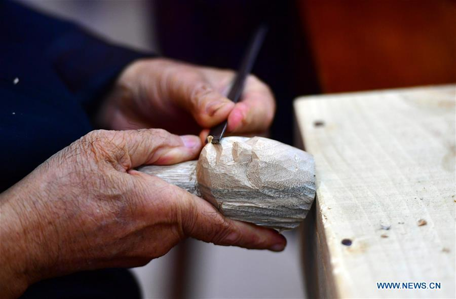 Xu Zhuchu, a national-level intangible cultural heritage inheritor of Zhangzhou wood puppet head carving, carves a puppet head at a studio in Zhangzhou City, southeast China\'s Fujian Province, Nov. 28, 2018. Listed as one of the national intangible cultural heritages in 2006, Zhangzhou wood puppet carving features exquisite craftsmanship. Xu\'s works of puppet head carving are known for rich and delicate facial expressions. Nowadays, Xu and his son, Xu Qiang, set up a studio of wood puppet to popularize local puppet culture. (Xinhua/Wei Peiquan)