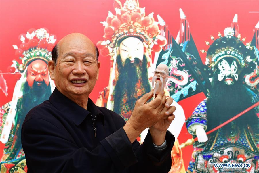 Xu Zhuchu, a national-level intangible cultural heritage inheritor of Zhangzhou wood puppet head carving, displays a wood puppet head at a studio in Zhangzhou City, southeast China\'s Fujian Province, Nov. 28, 2018. Listed as one of the national intangible cultural heritages in 2006, Zhangzhou wood puppet carving features exquisite craftsmanship. Xu\'s works of puppet head carving are known for rich and delicate facial expressions. Nowadays, Xu and his son, Xu Qiang, set up a studio of wood puppet to popularize local puppet culture. (Xinhua/Wei Peiquan)
