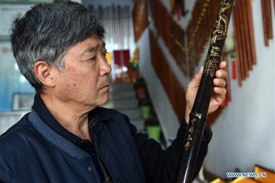 Liu Zesong, inheritor of the Yuping bamboo flute making craft, introduces a flute he made in Yuping Dong Autonomous County, southwest China\'s Guizhou Province, Nov. 29, 2018. As a traditional Chinese bamboo instrument, Yuping bamboo flute is famous for its clear tone and delicate carving. Made from local bamboo, the flute goes through dozens of procedures before finished and merges folk cultures of other ethnic groups. It was listed as one of the National Intangible Cultural Heritages in 2006. (Xinhua/Ma Ning)