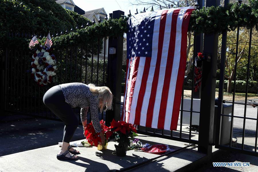 A woman lays flowers at the gate of the residence of former U.S. President George H.W. Bush in Houston, Texas, the United States, on Dec. 1, 2018. George H.W. Bush, the 41st president of the United States, has died Friday at the age of 94, according to a statement from his office. (Xinhua/Steven Song)