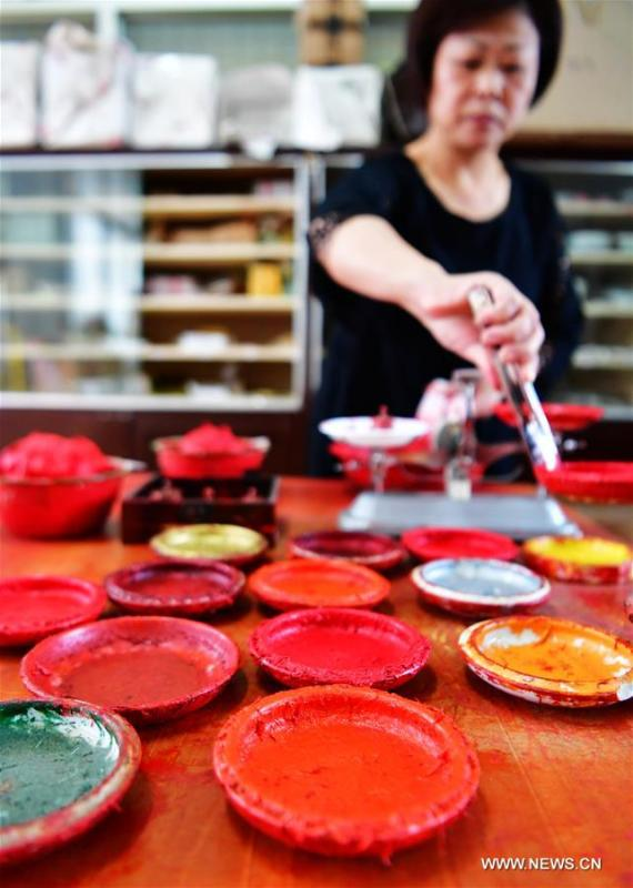 A worker fills Babao red ink paste into saucers in Zhangzhou, southeast China\'s Fujian Province, Nov. 30, 2018. Made of many precious materials such as pearl, agate, coral and musk, Zhangzhou red ink paste has been favoured by painters and calligraphers both home and abroad for over 300 years. Its making technology was listed as the second batch of national intangible cultural heritages in 2008. (Xinhua/Wei Peiquan)