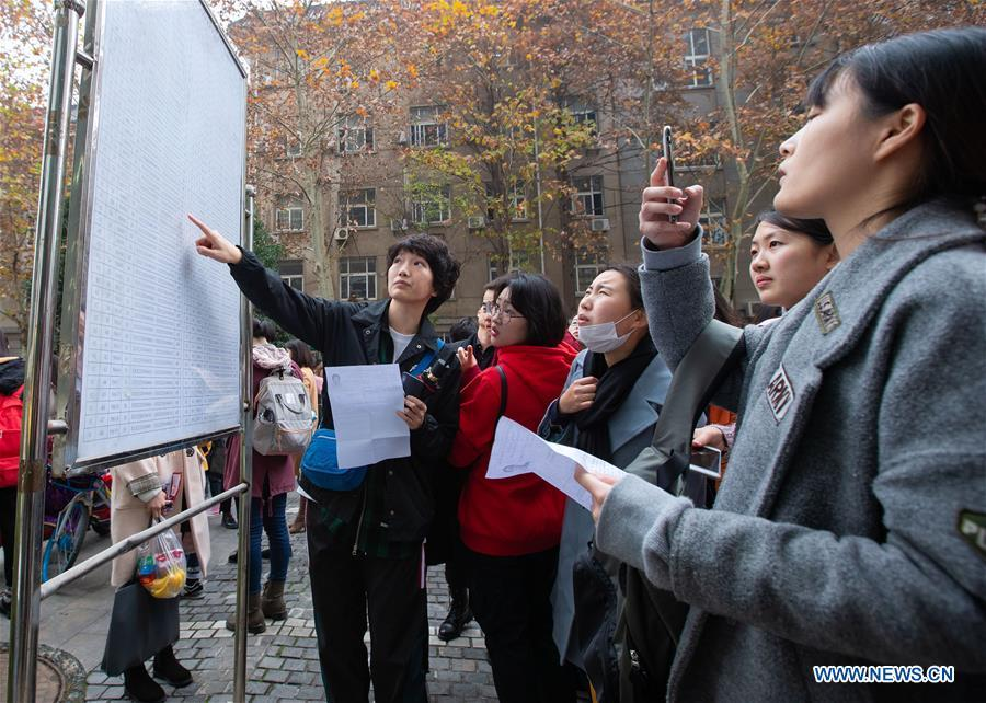 Candidates check exam information before taking the national civil servant exam at Nanjing Forestry University in Nanjing, capital of east China\'s Jiangsu Province, Dec. 2, 2018. The written exam of the national civil servant exam was held on Sunday across the country. (Xinhua/Su Yang)