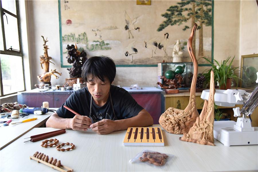 Zhu Haiyang does olive pit carving at his home in September of last year.  (Photo by Qian Lei for chinadaily.com.cn)
