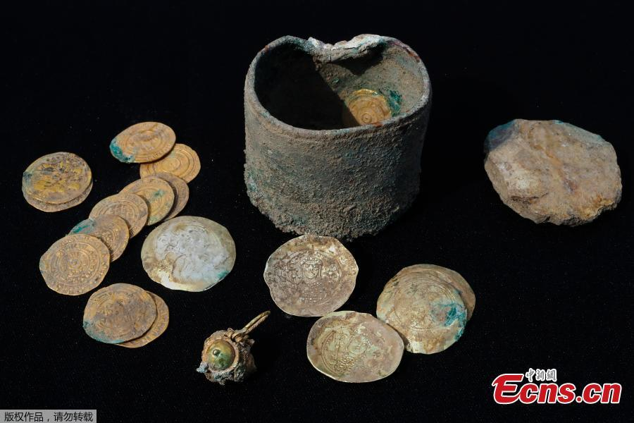 A picture taken on December 3, 2018, shows ancient gold coins and an earring recently uncovered at an excavation site in the Israeli Mediterranean town of Caesarea.  A treasure of 24 rare gold coins consisting of 18 Fatimid dinars, which were the standard local currency during that time (909-1171), as well as six are Byzantine coins, which include five dating to the era of Byzantine Emperor Michael VII Doukas (1071-1078), was recently uncovered in Caesarea. (Photo/Agencies)