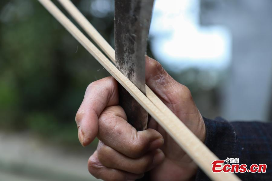 78-year-old Song Erfeng chops bamboo into long and thin filaments in preparation for materials to make bamboo hats in a village in Tangtou town, Southwest China\'s Guizhou province on December 3, 2018.  As an inheritor of bamboo hat making skills, Song has been practicing the craft for 70 years. Being made with bamboo filaments as thin as hair, the special hat has a history that can be traced back to Ming Dynasty (1368-1644). (Photo: China News Service/ Qu Honglun)