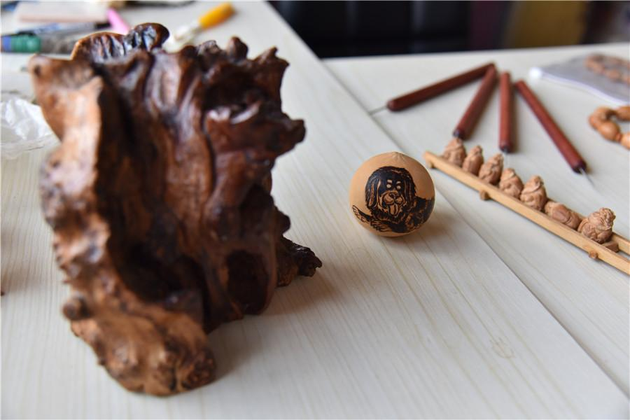 Artworks made of olive pits, carved by Zhu.  (Photo by Qian Lei for chinadaily.com.cn)