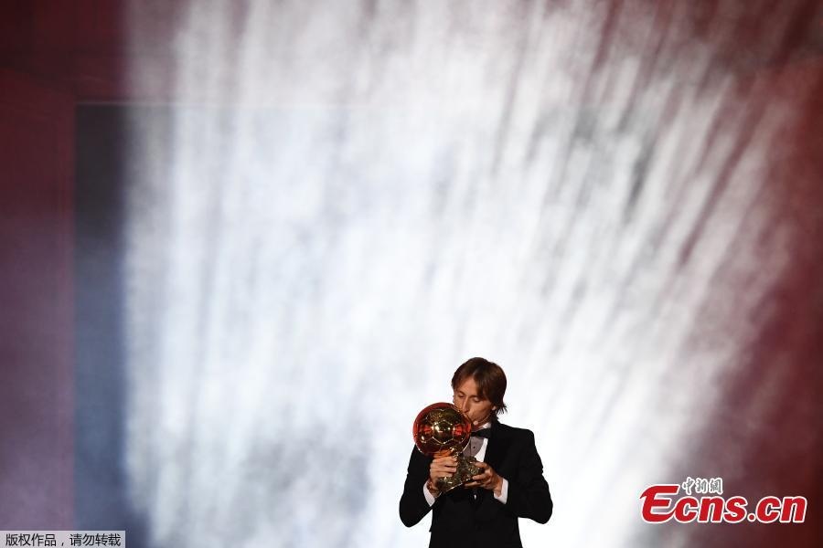 Real Madrid\'s Croatian midfielder Luka Modric kisses the trophy after receiving the 2018 FIFA Men\'s Ballon d\'Or award for best player of the year during the 2018 FIFA Ballon d\'Or award ceremony at the Grand Palais in Paris on December 3, 2018. The winner of the 2018 Ballon d\'Or will be revealed at a glittering ceremony in Paris on December 3 evening, with Croatia\'s Luka Modric and a host of French World Cup winners all hoping to finally end the 10-year duopoly of Cristiano Ronaldo and Lionel Messi.  (Photo/Agencies)