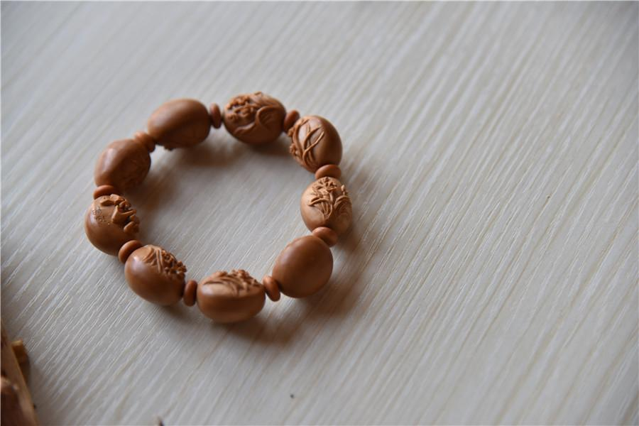 A bracelet made of olive pits, carved by Zhu. (Photo by Qian Lei for chinadaily.com.cn)
