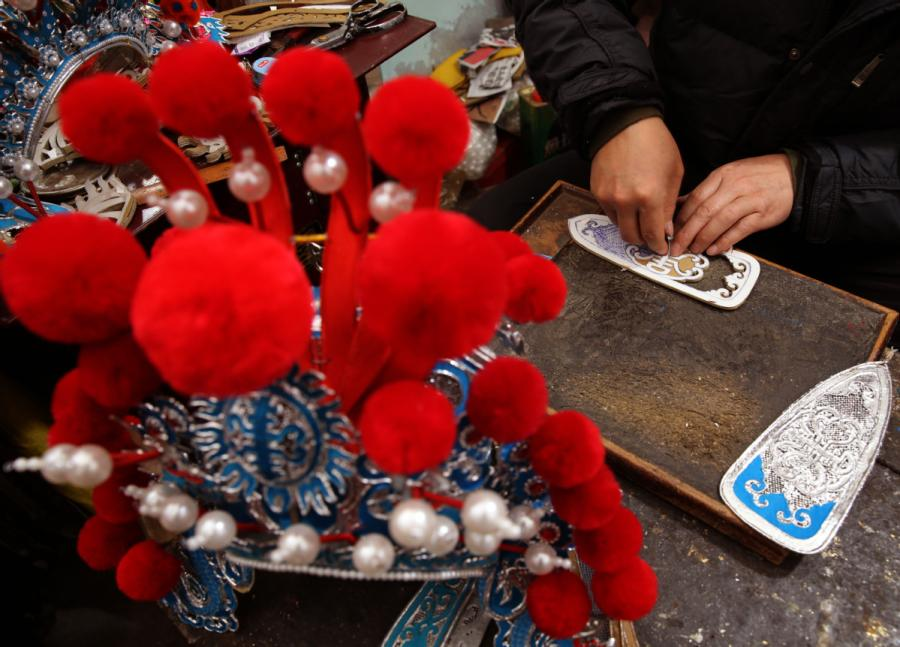 Han needs at least three days to finish a hand-made headwear piece.  (Photo by Huo Yan/chinadaily.com.cn)