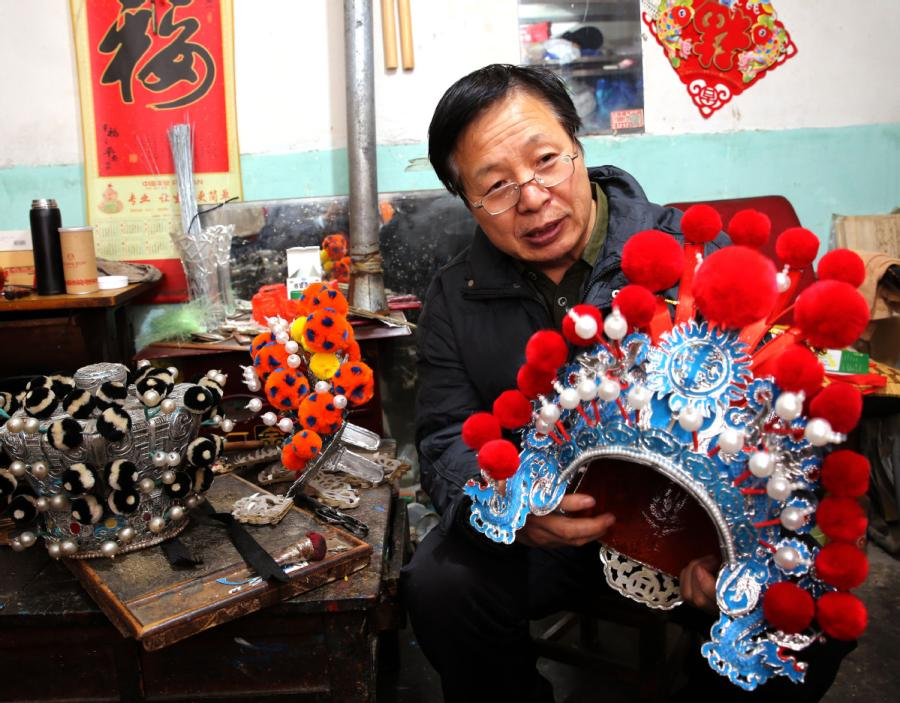Han Xiaoli presents a headwear piece he made. (Photo by Huo Yan/chinadaily.com.cn)