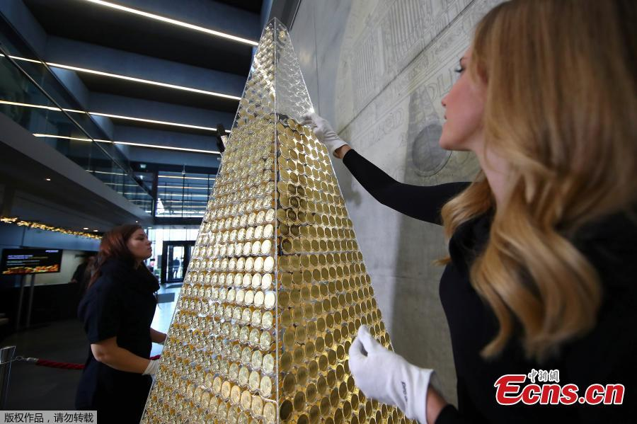 An employee of the ProAurum gold house decorates, what they say is Europe\'s most expensive Christmas tree, made of 2,018 Vienna philharmonic gold coins, valued at 2.3 million euros in Munich, Germany December 3, 2018. (Photo/Agencies)