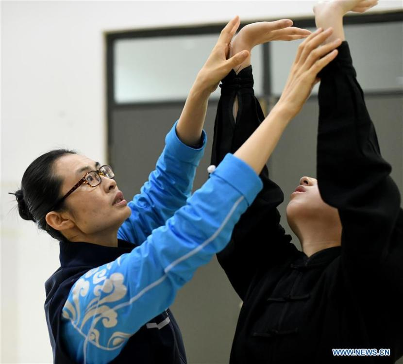 Huo Jinghong, the 5th generation descendant of Huo Yuanjia, a Chinese martial arts master, instructs a student to practice health Qigong, a traditional martial art combined with meditation, at Tianjin University of Commerce in Tianjin, north China, Nov. 26, 2018. As the descendant of Huo Yuanjia, one of China\'s most revered martial arts masters, Huo Jinghong, 41, started practicing martial arts at the age of 5. After her graduation from the Wushu School of Beijing Sport University in major of Wushu Routine, Huo started her career as a gym teacher of Tianjin University of Commerce in the year of 2000. As a gym teacher, Huo teaches martial arts for the university team and offers classes on health Qigong, a new form selected from different versions of traditional Qigong for modern fitness, in the university. Later in 2015, Huo became the inheritor of Huo-style boxing, which was listed as an intangible cultural heritage in Tianjin, and since then, she has devoted herself to the inheritance and development of the martial arts handed down from the older generation of Huo\'s family. She hoped that the Huo-style boxing would help people understand more about the Chinese martial arts. Huo Yuanjia was born in Tianjin in 1868. He founded the Chin Woo Athletic Association in 1910 in Shanghai and advocated the spirit of \