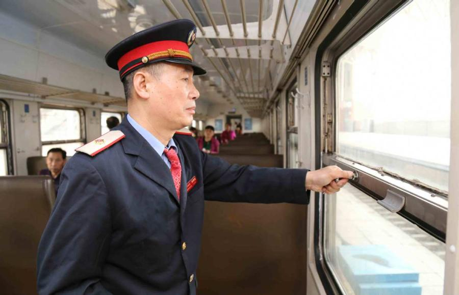 Sun Mingjin works on a green train that runs between the cities of Jilin and Tumen, Northeast China\'s Jilin Province.  (Photo by Qu Xiaoxi for chinadaily.com.cn)