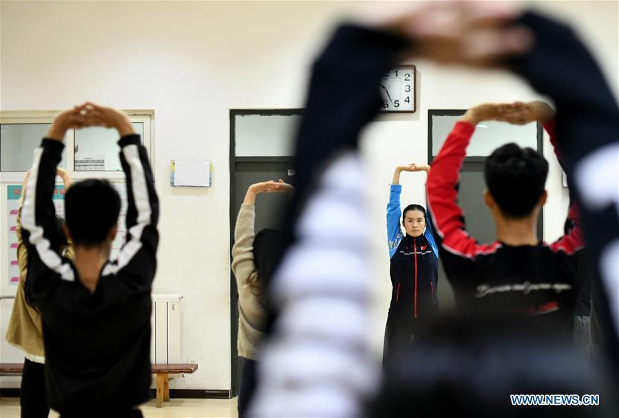 Huo Jinghong, the 5th generation descendant of Huo Yuanjia, a Chinese martial arts master, demonstrates health Qigong, a traditional martial art combined with meditation, for students at Tianjin University of Commerce in Tianjin, north China, Nov. 26, 2018. As the descendant of Huo Yuanjia, one of China\'s most revered martial arts masters, Huo Jinghong, 41, started practicing martial arts at the age of 5. After her graduation from the Wushu School of Beijing Sport University in major of Wushu Routine, Huo started her career as a gym teacher of Tianjin University of Commerce in the year of 2000. As a gym teacher, Huo teaches martial arts for the university team and offers classes on health Qigong, a new form selected from different versions of traditional Qigong for modern fitness, in the university. Later in 2015, Huo became the inheritor of Huo-style boxing, which was listed as an intangible cultural heritage in Tianjin, and since then, she has devoted herself to the inheritance and development of the martial arts handed down from the older generation of Huo\'s family. She hoped that the Huo-style boxing would help people understand more about the Chinese martial arts. Huo Yuanjia was born in Tianjin in 1868. He founded the Chin Woo Athletic Association in 1910 in Shanghai and advocated the spirit of \