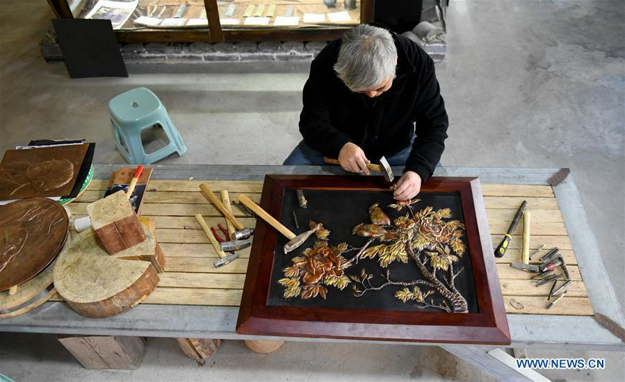 Guo Hailong, inheritor of welding-aided iron relief handicraft, works on an iron board at his workshop in Deming ancient town of Shijiazhuang, capital of north China\'s Hebei Province, on Dec. 4, 2018. The craftsmanship was listed as the provincial intangible cultural heritage in 2013. (Xinhua/Chen Qibao)