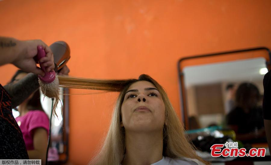 A hairstylist blow drys the hair of an inmate in preparation for the 13th annual Miss Talavera Bruce beauty pageant at the penitentiary the pageant is named for, in Rio de Janeiro, Brazil, Tuesday, Dec. 4, 2018. Hairdressers and makeup artists volunteer their time to ready the contestants who are judged on their beauty, appeal and attitude. (Photo/Agencies)