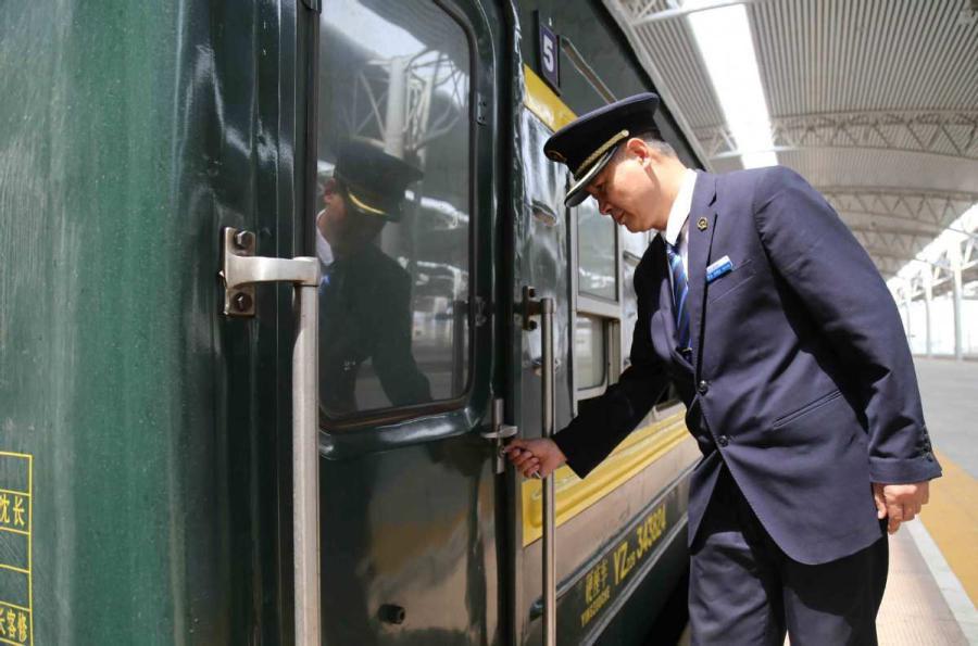 Sun Mingjin opens the door of a green train carriage. (Photo by Qu Xiaoxi for chinadaily.com.cn)