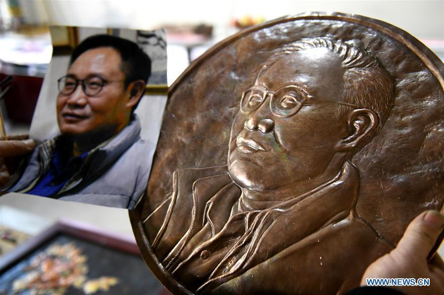 Guo Hailong, inheritor of welding-aided iron relief handicraft, checks a bust relief ordered by a customer at his workshop in Deming ancient town of Shijiazhuang, capital of north China\'s Hebei Province, on Dec. 4, 2018. The craftsmanship was listed as the provincial intangible cultural heritage in 2013. (Xinhua/Chen Qibao)