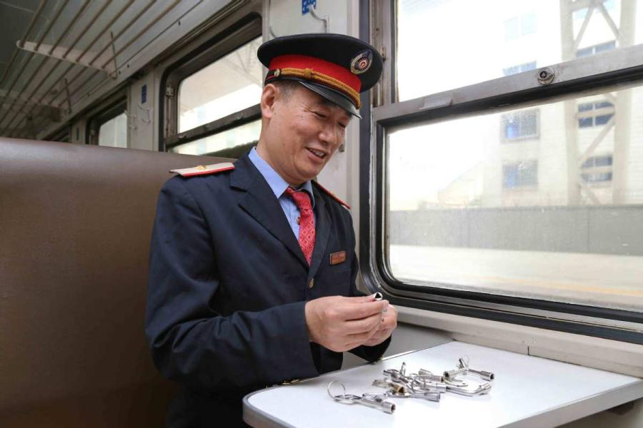 Sun Mingjin presents his collection of train keys. (Photo by Qu Xiaoxi for chinadaily.com.cn)