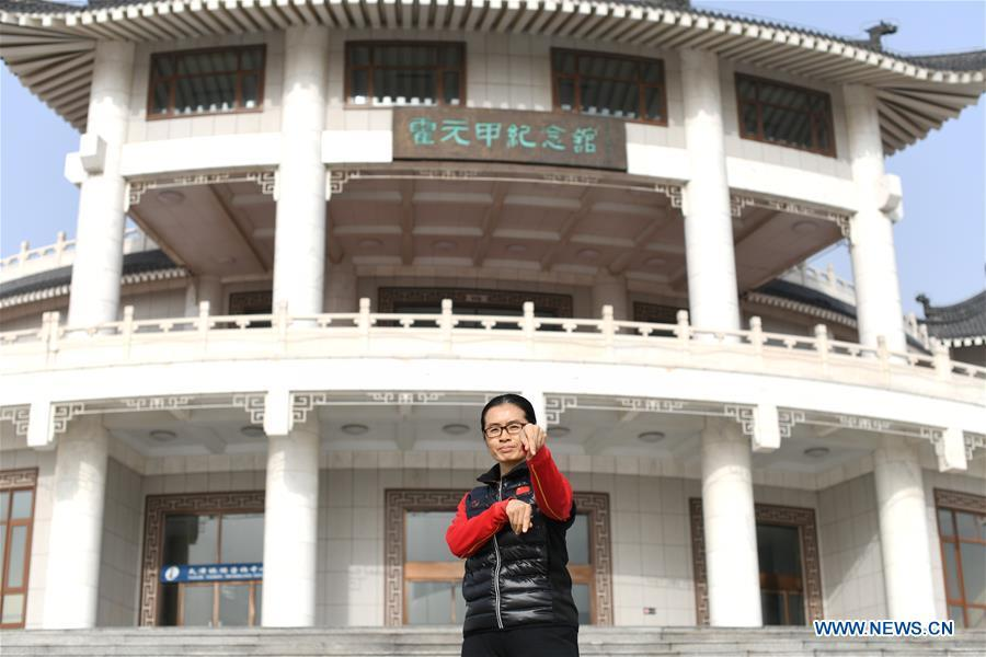 Huo Jinghong, the 5th generation descendant of Huo Yuanjia, a Chinese martial arts master, poses in front of Huo Yuanjia Memorial in Xiaonanhe Village of Jingwu Township in Tianjin, north China\'s Municipality, Nov. 28, 2018. As the descendant of Huo Yuanjia, one of China\'s most revered martial arts masters, Huo Jinghong, 41, started practicing martial arts at the age of 5. After her graduation from the Wushu School of Beijing Sport University in major of Wushu Routine, Huo started her career as a gym teacher of Tianjin University of Commerce in the year of 2000. As a gym teacher, Huo teaches martial arts for the university team and offers classes on health Qigong, a new form selected from different versions of traditional Qigong for modern fitness, in the university. Later in 2015, Huo became the inheritor of Huo-style boxing, which was listed as an intangible cultural heritage in Tianjin, and since then, she has devoted herself to the inheritance and development of the martial arts handed down from the older generation of Huo\'s family. She hoped that the Huo-style boxing would help people understand more about the Chinese martial arts. Huo Yuanjia was born in Tianjin in 1868. He founded the Chin Woo Athletic Association in 1910 in Shanghai and advocated the spirit of \