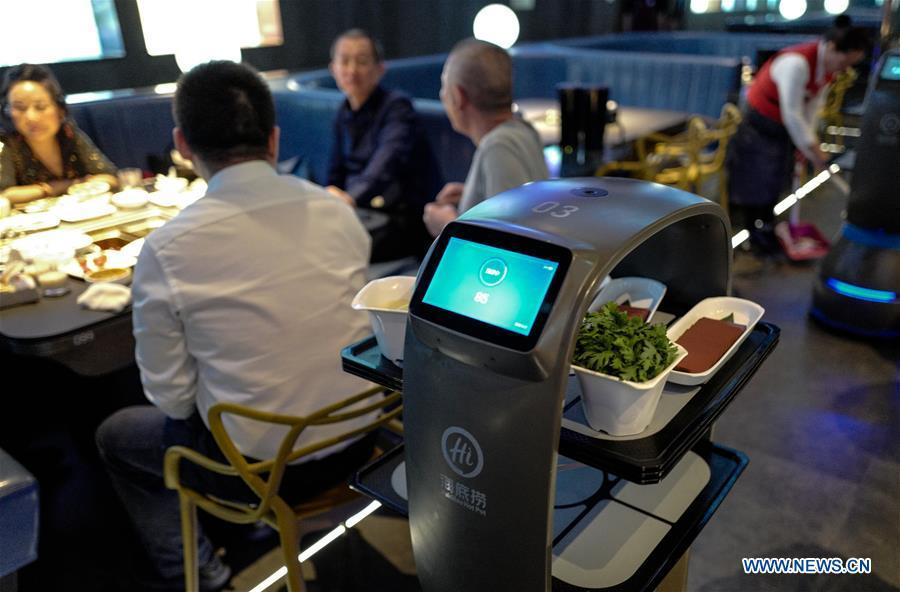 A delivery robot sends dishes to tables at a hot pot restaurant in Beijing, capital of China, Dec. 5, 2018. A hot pot restaurant which integrates artificial intelligence, big data management and smart robot service has attracted lots of consumers. After customers order their dishes with a tablet computer, robotic arms in the kitchen get all dishes ready and then the delivery robots sent the dishes to the tables. Workers in the kitchen control all the procedures and also monitor the data for better management. (Xinhua/Zhang Chen)
