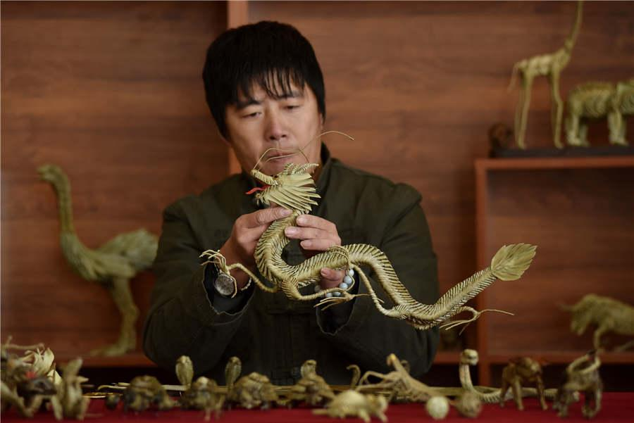 Craftsman Han Liuye works with one of his straw-plaited artworks on December 3 in Zhangjiakou, Hebei Province. (Photo provided to chinadaily.com.cn)