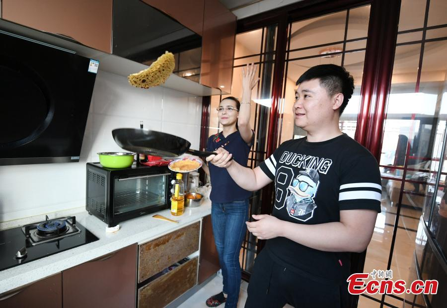 Valentina and her husband cook at home in Changchun, Northeast China's Jilin province. As a fan of Chinese food and culture, Valentina found her husband on the internet and then settled down in Changchun. Valentina said at the beginning she hosted live streams to get more chance to talk with audience, so as to learn Chinese better. After knowing the audience liked to watch her cooking and painting, Valentina started to broadcast her daily routines, and now she had over 200,000 followers. (Photo: China News Service/ Zhang Yao)
