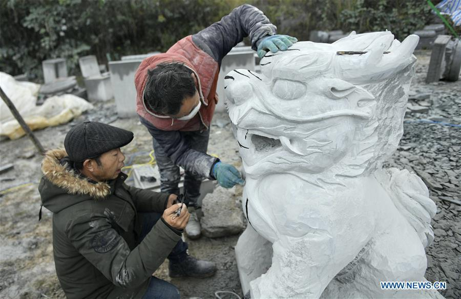 Two handicraftsmen process a rock carving work in Longdong Village of Xuan\'en County in Enshi Tujia and Miao Autonomous Prefecture, central China\'s Hubei Province, Dec. 5, 2018. Residents here benefit from the rich rock resources and turn plain rocks into delicate artworks. (Xinhua/Song Wen)