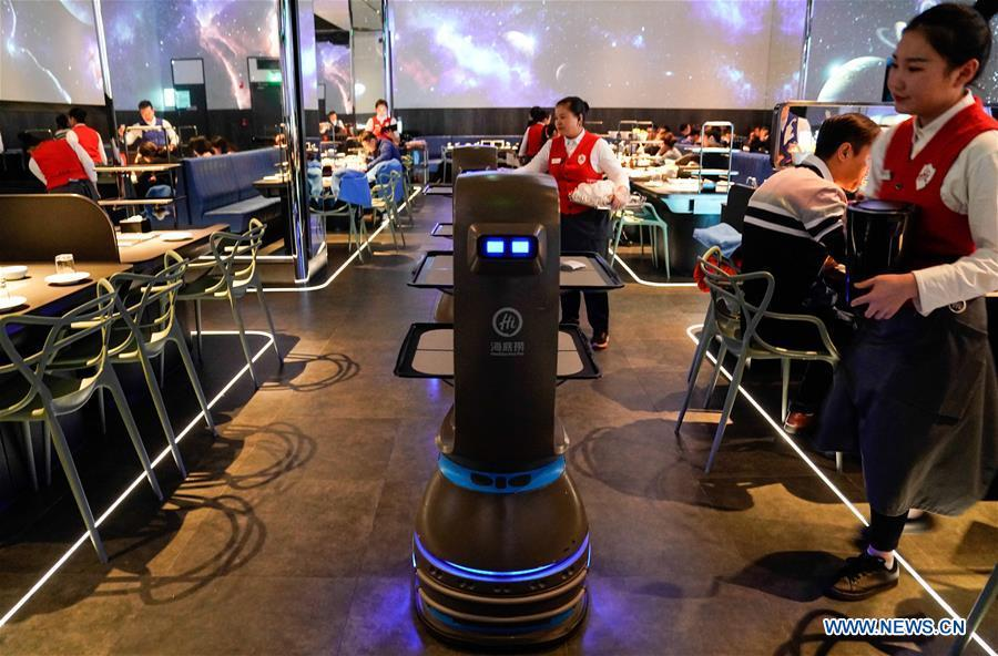 A delivery robot works at a hot pot restaurant in Beijing, capital of China, Dec. 5, 2018. A hot pot restaurant which integrates artificial intelligence, big data management and smart robot service has attracted lots of consumers. After customers order their dishes with a tablet computer, robotic arms in the kitchen get all dishes ready and then the delivery robots sent the dishes to the tables. Workers in the kitchen control all the procedures and also monitor the data for better management. (Xinhua/Chen Junqing)