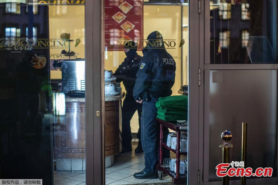 Masked police stand in an ice parlor in Duisburg, western Germany, Wednesday, Dec. 5, 2018 as authorities conduct coordinated raids in Germany, Italy, Belgium and the Netherlands in a crackdown on the Italian mafia. (Photo/Agencies)