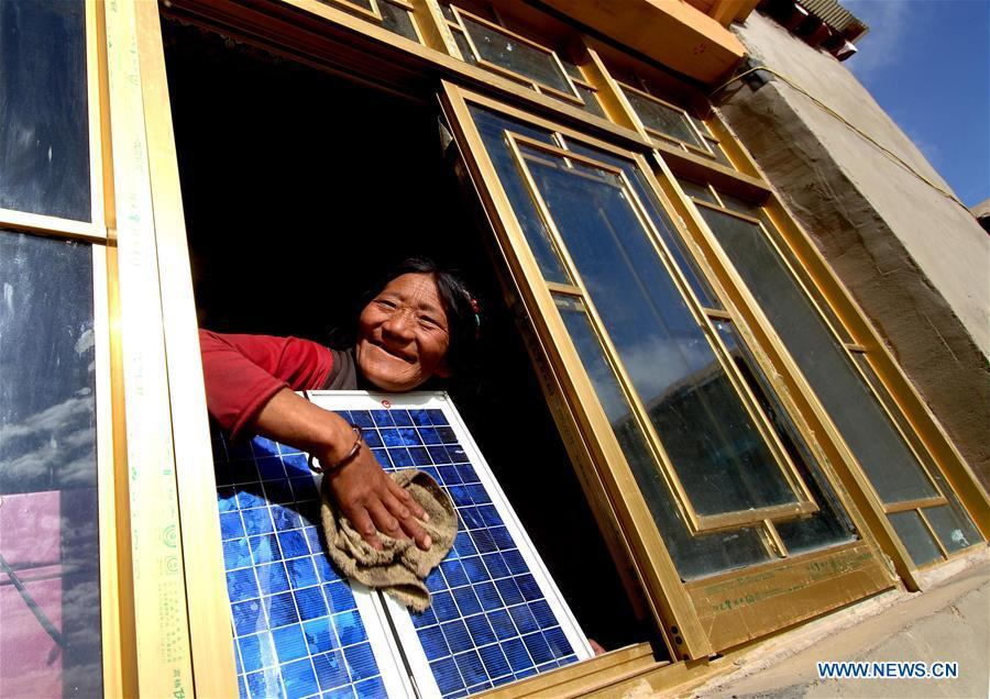 A woman cleans a solar panel at her new house thanks to the \