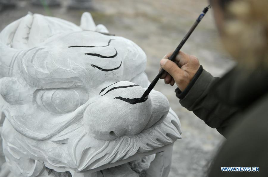A handicraftsman sketches on a rock carving work for further processing in Longdong Village of Xuan\'en County in Enshi Tujia and Miao Autonomous Prefecture, central China\'s Hubei Province, Dec. 5, 2018. Residents here benefit from the rich rock resources and turn plain rocks into delicate artworks. (Xinhua/Song Wen)