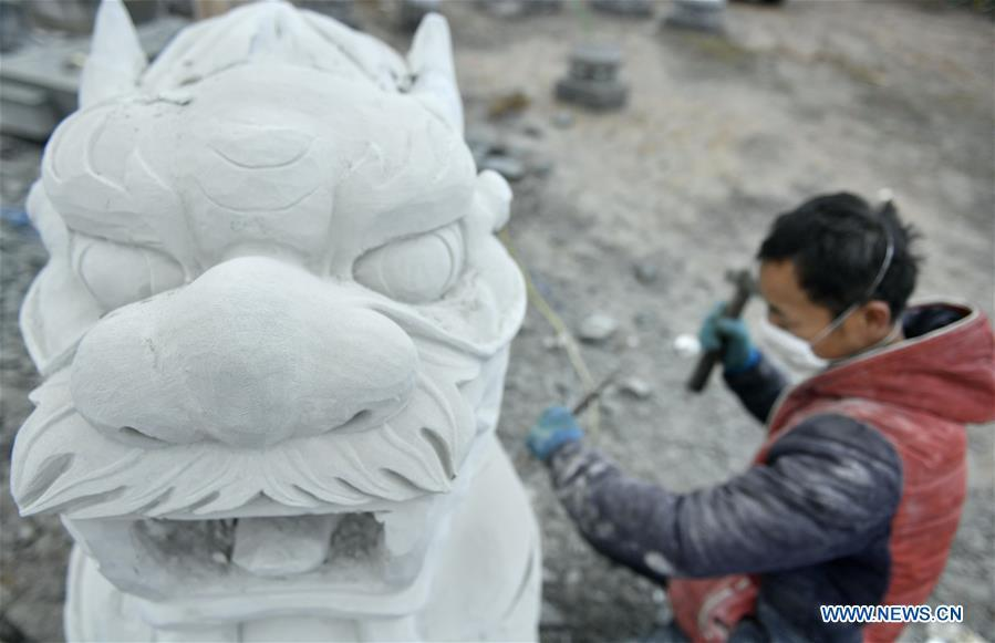 A handicraftsman processes a rock carving work in Longdong Village of Xuan\'en County in Enshi Tujia and Miao Autonomous Prefecture, central China\'s Hubei Province, Dec. 5, 2018. Residents here benefit from the rich rock resources and turn plain rocks into delicate artworks. (Xinhua/Song Wen)