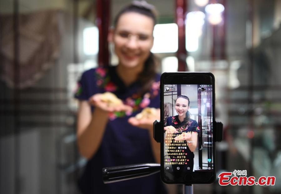 Valentina, a 26-year-old girl Russia speaks to her audience while making dumplings through live video streaming platforms at her home in Changchu, Northeast China's Jilin province. As a fan of Chinese food and culture, Valentina found her husband on the internet and then settled down in Changchun. Valentina said at the beginning she hosted live streams to get more chance to talk with audience, so as to learn Chinese better. After knowing the audience liked to watch her cooking and painting, Valentina started to broadcast her daily routines, and now she had over 200,000 followers. (Photo: China News Service/ Zhang Yao)