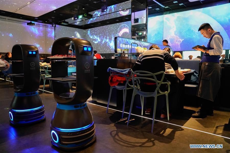Delivery robots send dishes to tables at a hot pot restaurant in Beijing, capital of China, Dec. 5, 2018. A hot pot restaurant which integrates artificial intelligence, big data management and smart robot service has attracted lots of consumers. After customers order their dishes with a tablet computer, robotic arms in the kitchen get all dishes ready and then the delivery robots sent the dishes to the tables. Workers in the kitchen control all the procedures and also monitor the data for better management. (Xinhua/Chen Junqing)