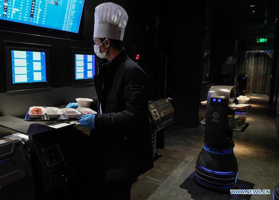 A delivery robot and a waiter work at the kitchen of a hot pot restaurant in Beijing, capital of China, Dec. 5, 2018. A hot pot restaurant which integrates artificial intelligence, big data management and smart robot service has attracted lots of consumers. After customers order their dishes with a tablet computer, robotic arms in the kitchen get all dishes ready and then the delivery robots sent the dishes to the tables. Workers in the kitchen control all the procedures and also monitor the data for better management. (Xinhua/Chen Junqing)