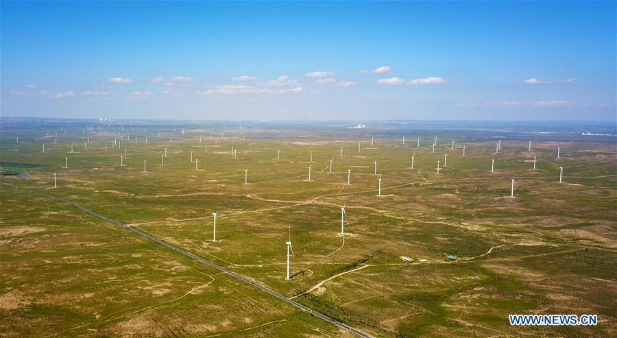 Aerial photo taken on Aug. 24, 2018 shows the Taiyangshan wind power station in the city of Wuzhong, northwest China\'s Ningxia Hui Autonomous Region. China has been delivering on its commitment to the international community on climate change by continuously shifting to a more green economy over the past years. New energy-rich regions like Inner Mongolia and Ningxia are sending more electricity generated from clean energy to the country\'s bustling east to help reduce the country\'s heavy reliance on coal in the fight against pollution and coping with climate change. China is also a leader in new energy vehicles (NEVs), with many regions across the country moving to replace their traditional gasoline-powered buses and taxis with green-energy vehicles. The country has been the world\'s largest NEV market for three consecutive years, with some 777,000 NEVs sold in 2017 alone. Sales in the first 10 months of this year jumped 75.6 percent year on year to 860,000 units. Thanks to increased investment in green energy, China\'s carbon intensity, or the amount of carbon dioxide emissions per unit of GDP, in 2017 had declined by 46 percent from 2005 levels, meeting the target ahead of schedule of a 40-45 percent drop by 2020, according to the Chinese Ministry of Ecology and Environment. (Xinhua/Guo Xulei)